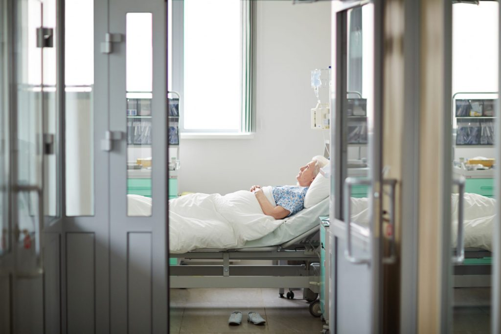 A son sits by his mother's bedside holding her hand as she nears the end of her life. His heart is breaking, there will be such a hole in his family's world. In the hallway outside her hospital room, the son can hear laughing and carts rolling around. He thinks to himself: does no one care that his mother is dying? Where's the respect and solitude that they need right now...
